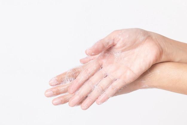 De aziatische meisjeshanden wassen met zeepbels op witte muur