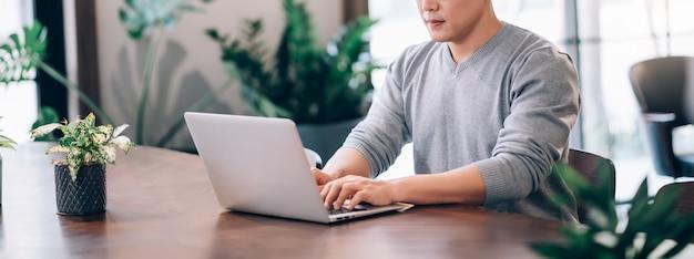 De aziatische mens die laptop computer met behulp van verbindt met hoge snelheid internet 5g draadloze verbindingstechnologie het werk vanuit huis