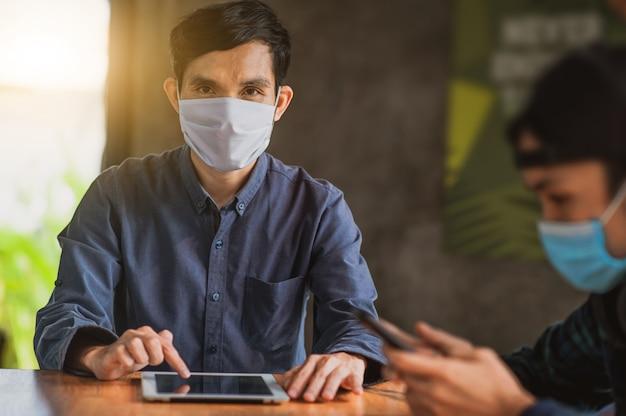 De aziatische mens die tablet gebruiken online werkend een dragend gezichtsmasker beschermt levensstijl nieuwe normaal van het coronavirus, mens levend in koffie binnen