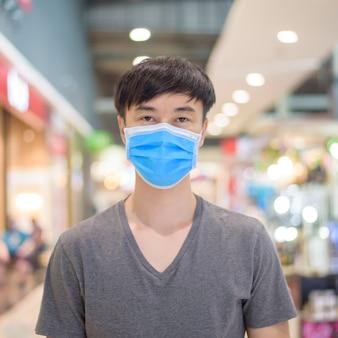 De aziatische mens draagt chirurgisch masker in winkelcomplex