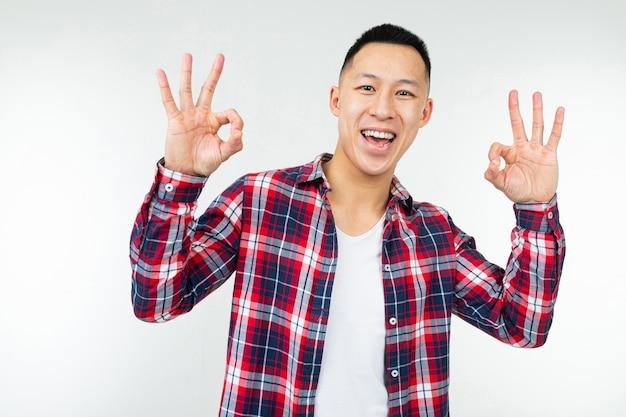 De aziatische mens in een wijd open geruit overhemd toont super op een geïsoleerde witte studio