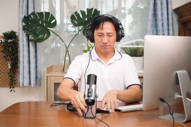 De aziatische mens in glazen die hoofdtelefoons met computer draagt, bereidt zich voor om videogesprek te voeren