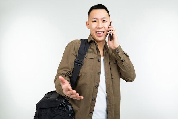 De aziatische mens in stedelijke kleren met een zak communiceert gebruikend een smartphone over zaken op een witte achtergrond