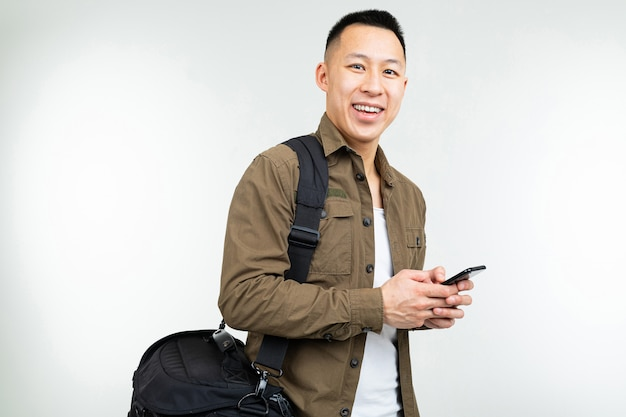 De aziatische mens in stedelijke kleren met een zak met een vrukhtelefoon gaat op een wit