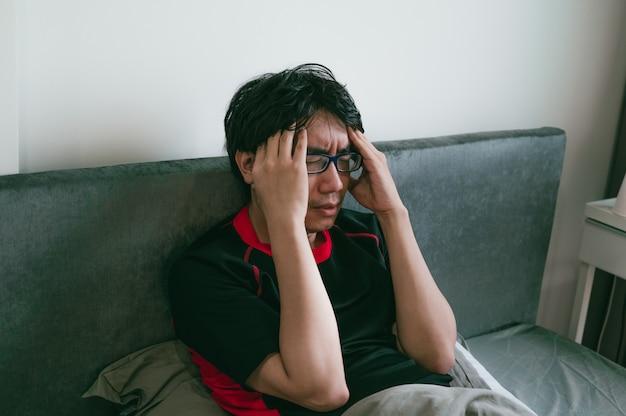 De aziatische mens is hoofdpijn en gebruikt zijn handen om hoofd te houden