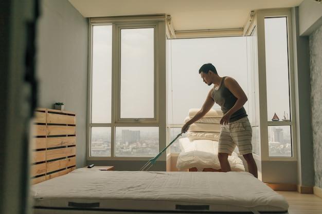 De aziatische mens maakt zijn slaapkamer met warm de zomerlicht schoon.