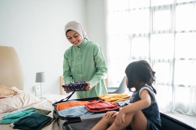 De aziatische moeder bereidt kleren voor die samen met haar dochter moeten worden weggenomen