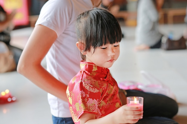 De aziatische moeder en de dochter in traditionele kleding steken de vereringskaarsen aan bij chinese tempel