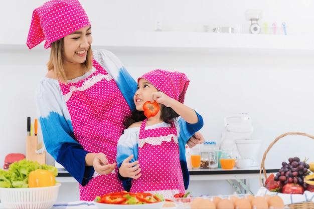 De aziatische moeder en de dochter koken samen ontbijt in keukenruimte.