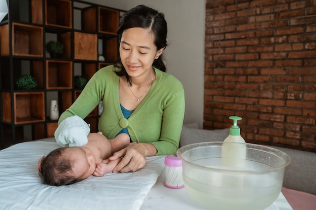 De aziatische moeder wrijft haar meisje gebruikend natte handdoek