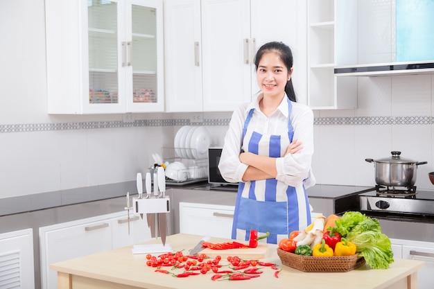 De aziatische mooie jonge vrouw in kok mengt beslag.