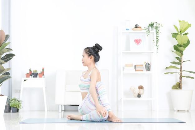 De aziatische mooie sportenvrouw voert thuis de oefeningen uit.