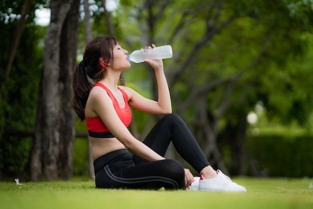 De aziatische mooie vrouwenzitting voor ontspant na training alleen en drinkwater van fles in openbaar park in dorp.