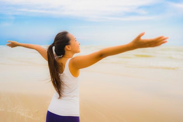 De aziatische oefeningsoefening van de portret mooie jonge door te lopen en op het openluchtaardstrand en het overzees te joggen