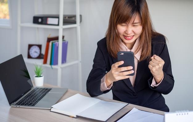 De aziatische onderneemster kijkt gelukkig terwijl het bekijken van de informatie op de telefoon
