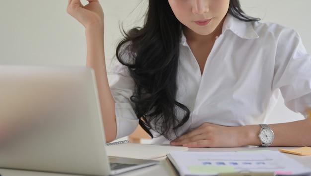 De aziatische onderneemster met een in hand pen controleert de bedrijfprestaties.