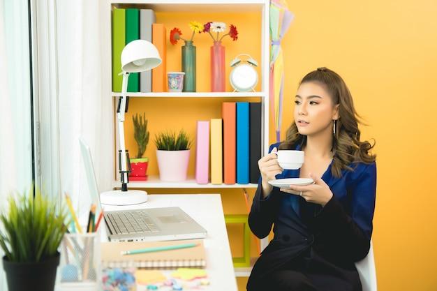 De aziatische onderneemster neemt een koffiepauze na het werken bij laptop computer aan bureau