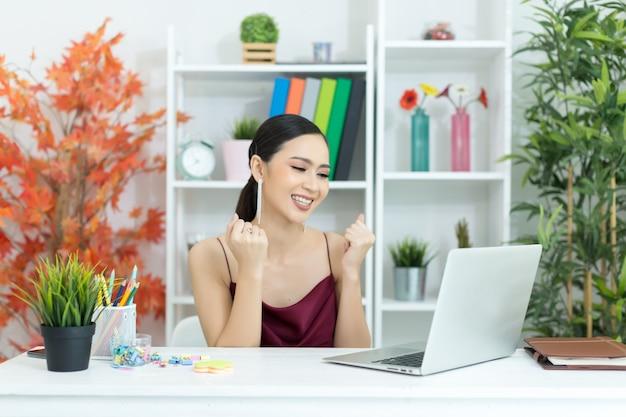 De aziatische onderneemster neemt een koffiepauze na het werken bij laptop computer op bureau