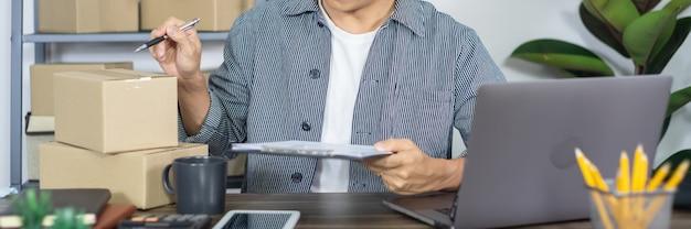 De aziatische ondernemer van het bedrijfsmensen startende mkb of het freelance werken in een kartondoos bereidt leveringsdoos voor klant, online verkoop, elektronische handel, verpakking en verschepend concept voor.