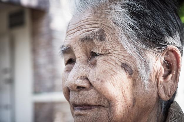 De aziatische oude bejaarde grootmoeder die van jaren '90 alleen bij openlucht glimlachen