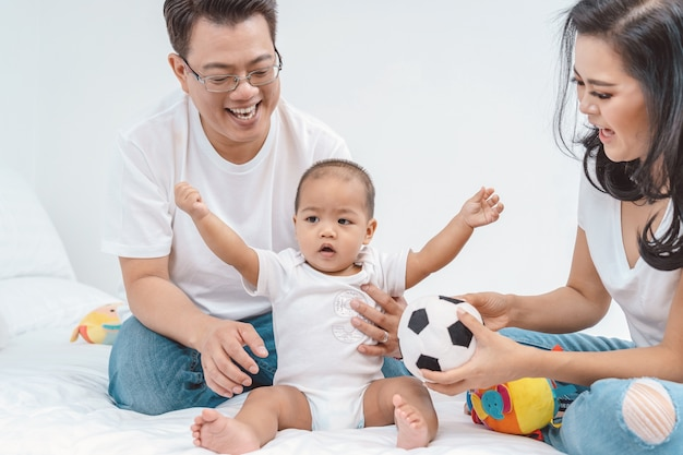 De aziatische scène van de gelukfamilie van jongensbaby met vader en moeder in de slaapkamer van huis