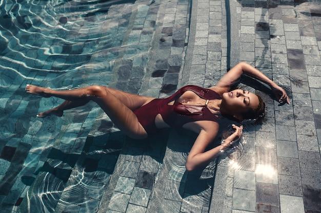 De aziatische sexy vrouw in de bikini van bourgondië bij zwembad op een zonnige dag, heldere toon, manierbikini stelt