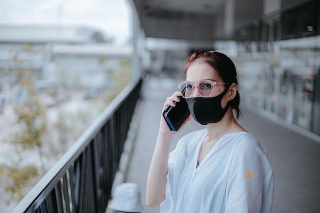 De aziatische smartphone van het vrouwengebruik met medisch masker op de stadsstraat.