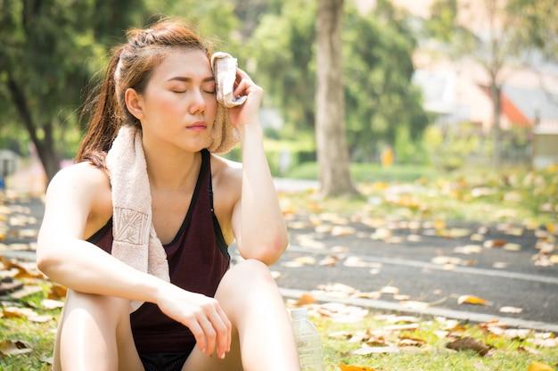 De aziatische sportvrouw wordt geprobeerd en rust na het lopen in park