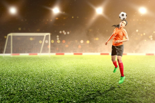 De aziatische sprong van de voetbalstervrouw en het leiden van de bal op de lucht op het voetbalgebied