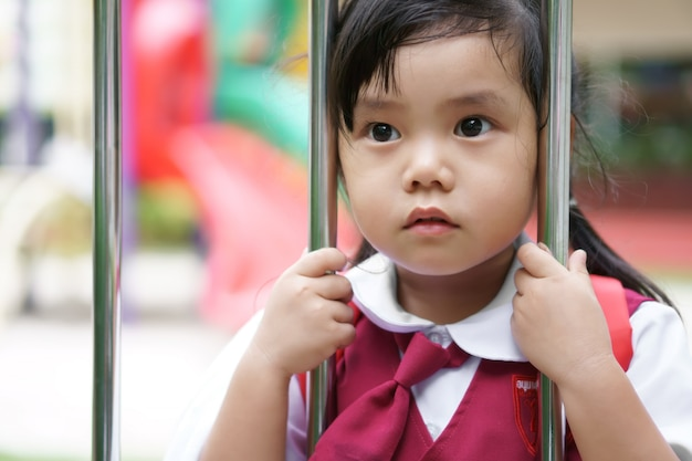 De aziatische studente draagt schooluniform en gaat naar school en houdt roestvrij staalomheining