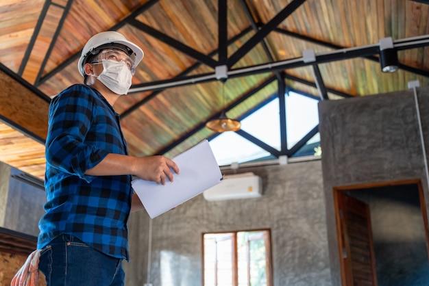 De aziatische technicus van de bouwingenieur inspecteert de houtstructuur onder het dak op de bouwplaats of de bouwplaats van een huis.