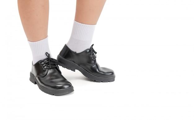 De aziatische thaise student van de jongeschool draagt een zwarte leerschoenen