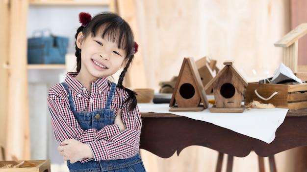 De aziatische timmerman die van het jong geitjemeisje aan houtbewerkingslijst werken in de winkel van het huistimmerwerk