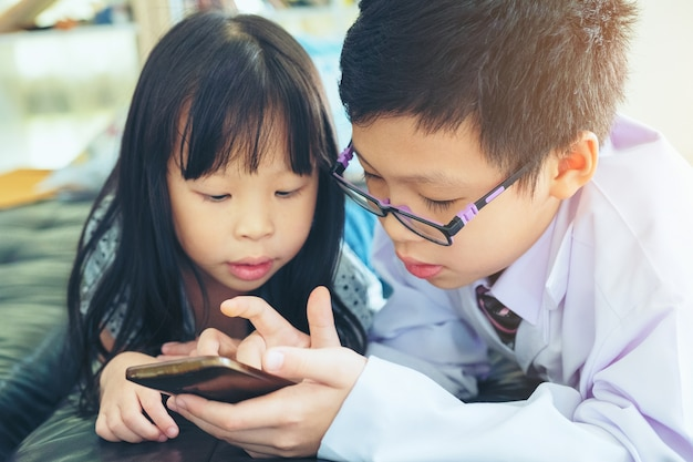De aziatische twee kinderenjongen en het meisje zitten samen op bed lettend op en spelen met smartphone
