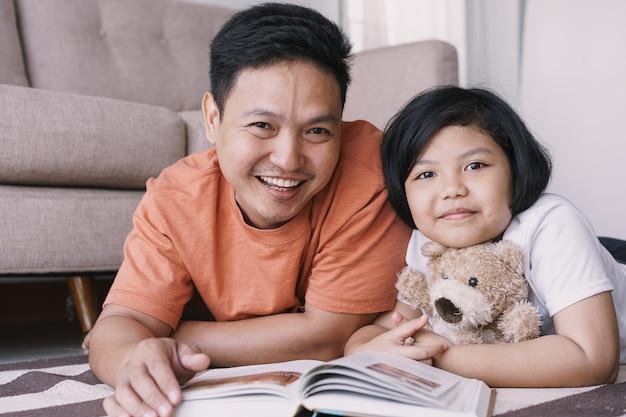 De aziatische vader en de dochter lezen boek terwijl liggend op het tapijt in de woonkamer bij haar huis. het schattige kleine meisje knuffelt de pop en lacht vrolijk met zijn vader.