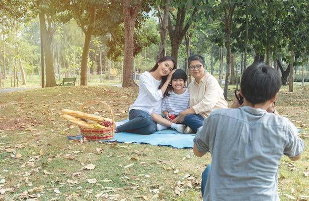 De aziatische vader gebruikt digitale camera neemt foto van zijn vrouw en zoon en oma in park. de vrije tijd van de familie van azië heeft picknick in park en neemt samen groepsfoto.