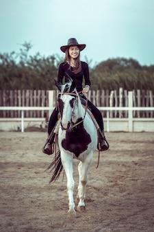 De aziatische veedrijfster die een paard berijdt.
