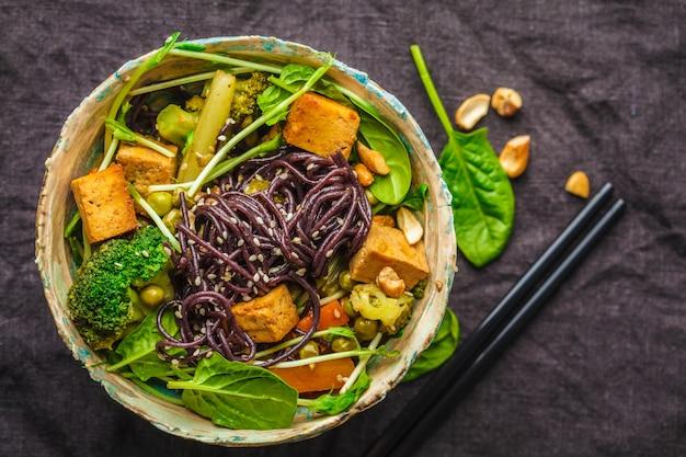 De aziatische veganist beweegt gebraden gerecht met tofu, rijstnoedels en groenten, donkere achtergrond.
