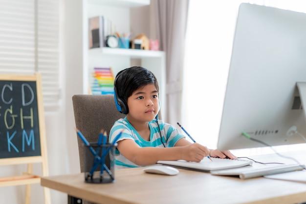 De aziatische videoconferentie van de jongensstudent e-leert met leraar op computer in woonkamer thuis