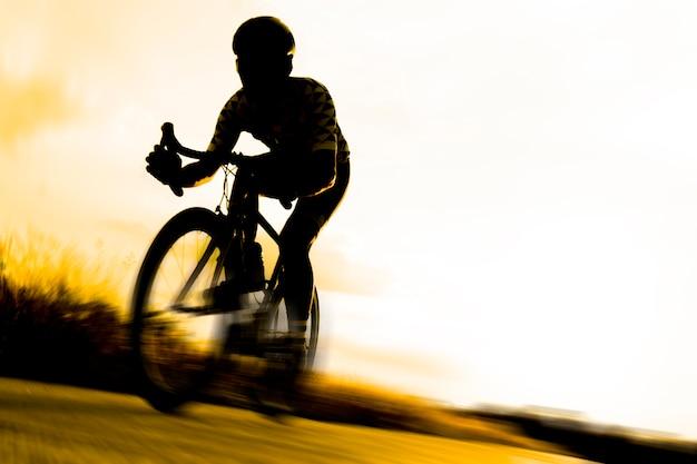 De aziatische volwassen fietser berijdt moderne fiets. silhouetfotografie.