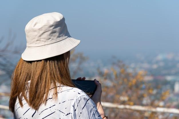 De aziatische vrij leuke vrouw met hoed ontspant bij het landschapsgezichtspunt van de kuststad op berg
