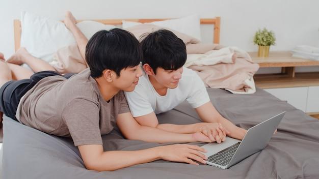 De aziatische vrolijke lgbtq mensen koppelen het gebruiken van computerlaptop bij modern huis. jonge de minnaar mannelijke gelukkig van azië ontspant samen rust na kielzog, lettend op film liggend op bed in slaapkamer bij huis in de ochtend.