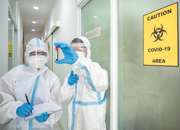 De aziatische vrouw arts in persoonlijk beschermend kostuum met masker schrijft op de quarantainepatiëntgrafiek, houdt bloedmonster voor onderzoek coronavirus met covid-19 gebieds alert teken.