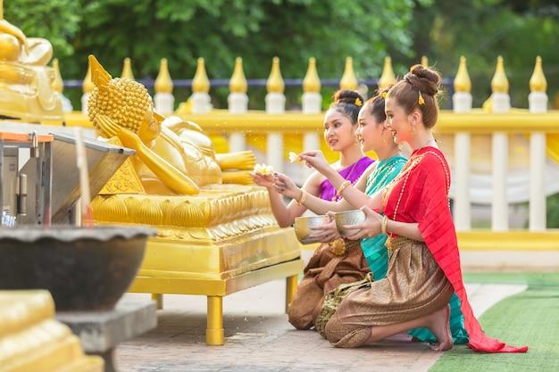 De aziatische vrouw baadt het standbeeld van boedha gelukkig in thailand.