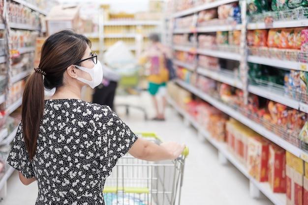 De aziatische vrouw die beschermend masker draagt en in supermarkt of kruidenierswinkel winkelt, beschermt coronavirusverbuiging. sociale afstand, nieuw normaal en leven na covid-19 pandemie