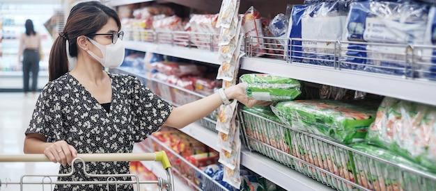 De aziatische vrouw die beschermend masker dragen en voedingsmiddelen houden tijdens het winkelen in supermarkt of kruidenierswinkel, beschermt verbuiging coronavirus. sociale afstand, nieuw normaal en leven na covid-19 pandemie