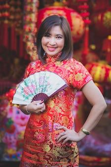 De aziatische vrouw die chinese vrouwentraditie draagt kleedt toothy het glimlachen gezicht in de stad van bangkok china van de yaowaratstraat