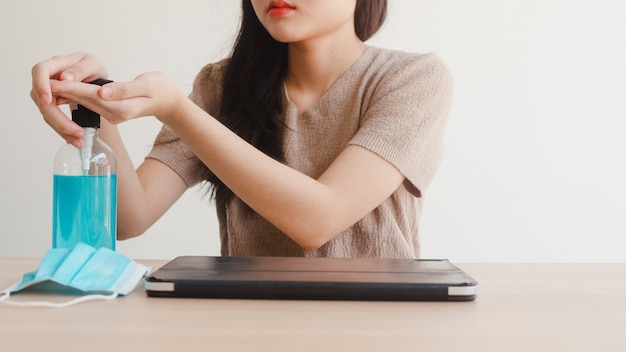 De aziatische vrouw die de hand van het het desinfecterende middelwas van de alcoholgel gebruiken vóór open tablet voor beschermt coronavirus. vrouw duwt alcohol om schoon te maken voor hygiëne bij sociale afstand thuisblijven en zelfquarantainetijd