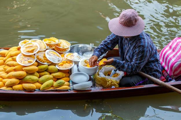 De aziatische vrouw die de mango's pellen is voor verkoop thais dessert