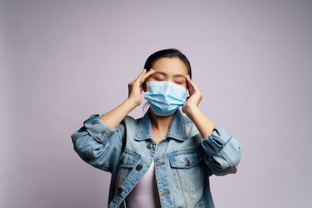 De aziatische vrouw die een beschermend gezichtsmasker droeg, was ziek met geïsoleerde hoofdpijn.